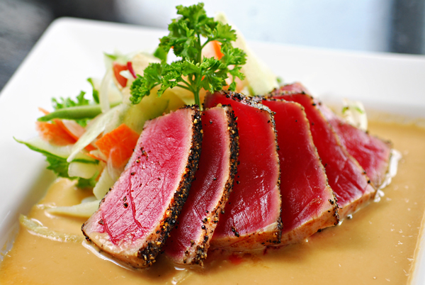Seared Ahi tuna with a reduced balsamic glaze on white plate